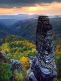 Piaskowa szczyt wzrastający od kolorowego lasowego tła niebo jest pomarańcze należnym wschód słońca. zdjęcie stock