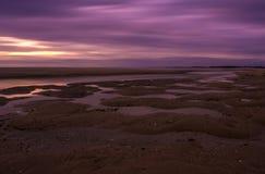 Piaskowata haczyk plaża przy zmierzchem zdjęcie stock