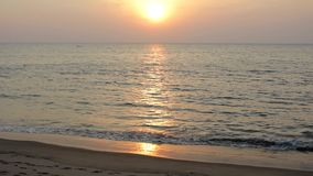Piaskowata plaża na tle łódź w oceanie i pogodnej ścieżce pod wieczór zmierzchu niebem zbiory
