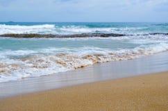 Piaskowata plaża z tła zamazanymi fala zdjęcia stock