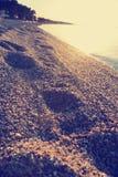 Piaskowata plaża przy zmierzchem z odciskami stopy na piasku; zatarty, retro styl, Fotografia Stock