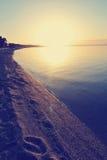 Piaskowata plaża przy zmierzchem z odciskami stopy na piasku; zatarty, retro styl, Zdjęcie Stock
