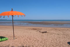 Piaskowatej plaży, niebieskiego nieba i pomarańcze parasol przy wschodnią punkt rezerwą, Zdjęcia Royalty Free