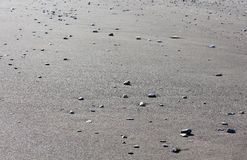 Piaskowatej plaży tło z małymi kamieniami Zdjęcie Stock