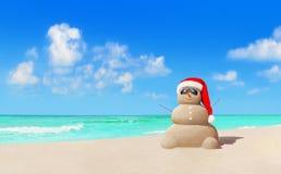 Piaskowaty bałwan w Bożenarodzeniowym Santa kapeluszu, okularach przeciwsłonecznych przy plażą i fotografia royalty free