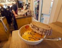 Piastra riscaldante di minestra e di pane dentro un caffè dell'via-alimento con il menu locale Immagini Stock Libere da Diritti