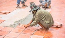 Piastrella per pavimento ed installazione di riparazione del lavoratore per la costruzione di casa Fotografie Stock