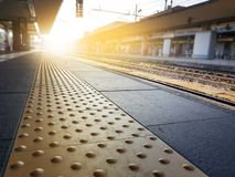 Piastrelle per pavimento cieche sul binario della stazione ferroviaria fotografia stock