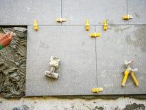 Piastrelli il lavoro che dispone la piastrella per pavimento ceramica dentro con le mattonelle della sferza che livellano il sist immagine stock