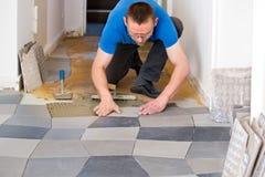 Piastrellista che dispone le nuove piastrelle per pavimento Fotografia Stock