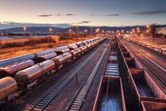 Piattaforma del treno del carico al tramonto con il contenitore fotografie stock