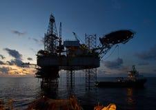 Piattaforma dell'impianto offshore con il bello cielo durante il tramonto Immagini Stock
