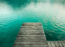 Piattaforma di legno come piattaforma del pilastro del ponte su un lago alpino con bella acqua verde della radura del turchese immagini stock libere da diritti