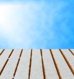 Piattaforma di legno con il fondo del cielo e della neve. Fotografie Stock Libere da Diritti