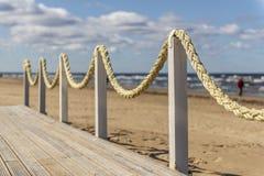 Piattaforma di legno con le corde sulla spiaggia, tempo nuvoloso, la costa baltica, Jurmala immagine stock