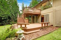 Piattaforma di legno dell'uscire in segno di disapprovazione con il patio ed i banchi Immagine Stock