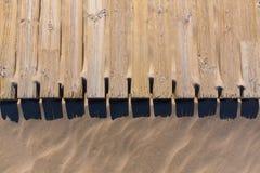 Piattaforma di legno di pino stagionata nella struttura della sabbia della spiaggia Fotografie Stock