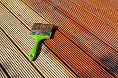 Piattaforma di legno di verniciatura del patio con olio protettivo immagine stock libera da diritti