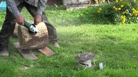 Piattaforma di legno stridente della mano maschio con l'ingranaggio elettrico della carta vetrata 4K video d archivio
