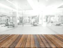 Piattaforma di spazio vuota del bordo di legno con la palestra di forma fisica della sfuocatura immagine stock