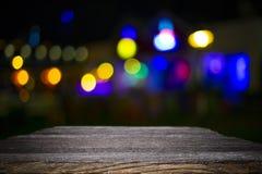 Piattaforma e bokeh di legno dello scrittorio alla notte fotografia stock