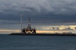 Piattaforma petrolifera e generatore eolico al tramonto immagine stock