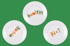 Piatti bianchi con il vegano di parole, in buona salute, dieta fatta dei pezzi di verdure su fondo verde Un insieme di tre immagi Fotografie Stock Libere da Diritti