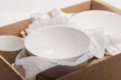 Piatti bianchi puliti in carta imballata in una scatola di cartone Rilocazione di concetto fotografie stock