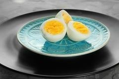 Piatti ceramici con gli uova sode affettati sulla tavola fotografia stock