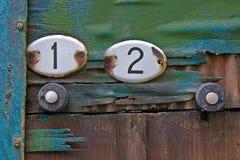 Piatti con i numeri degli appartamenti su una vecchia porta Immagini Stock Libere da Diritti