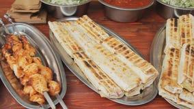 Piatti con la pita, la carne arrostita e le patate sugli spiedi Pollo arrostito e verdure al mercato Carne del barbecue a video d archivio