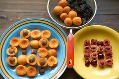 Piatti con le albicocche e ciliege e colapasta in pieno delle bacche Fotografia Stock Libera da Diritti