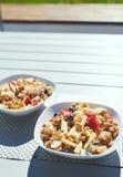 Piatti con macedonia, Granola e le bacche freschi di mattina sulla veranda Fotografia Stock Libera da Diritti