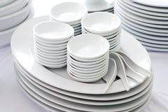 Piatti, cucchiaio e ciotola bianchi Immagini Stock