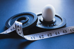 Piatti d'acciaio di sollevamento pesi con la misura di nastro ed un uovo sodo bianco Fotografia Stock