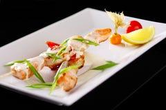 Piatti del ristorante con gli spiedi dei frutti di mare con il salmone ed il gamberetto fotografie stock