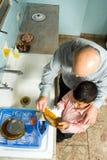 Piatti della lavata del nipote e del nonno. Fine in su - H Immagini Stock