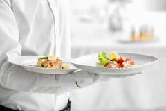 Piatti della tenuta del cameriere con i piatti, Fotografia Stock Libera da Diritti