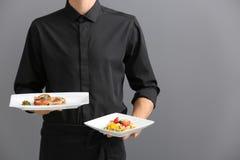 Piatti della tenuta del cameriere con i piatti Immagini Stock Libere da Diritti