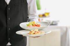 Piatti della tenuta del cameriere con i piatti al banchetto, Immagine Stock