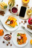Piatti delle cialde belghe con il cachi, i semi del melograno e la panna acida Fotografie Stock Libere da Diritti