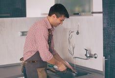 Piatti di lavaggio dell'uomo in cucina fotografia stock