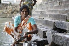 Piatti di lavaggio della donna indiana nel fiume Immagini Stock