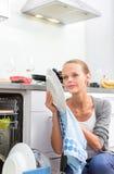 Piatti di lavaggio della giovane donna nella sua cucina moderna Immagine Stock