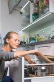 Piatti di lavaggio della giovane donna nella sua cucina moderna Fotografie Stock