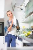 Piatti di lavaggio della giovane donna nella sua cucina moderna Fotografia Stock Libera da Diritti