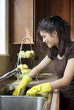 Piatti di lavaggio della ragazza teenager al dispersore di cucina Immagine Stock Libera da Diritti
