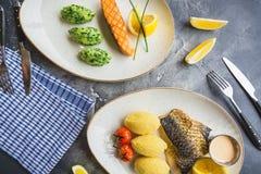 Piatti di pesce con il porridge del miglio, il pomodoro, la fetta del limone e la salsa di gamberetto sulla tavola scura Fotografia Stock
