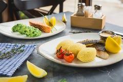 Piatti di pesce con il porridge del miglio, il pomodoro, la fetta del limone e la salsa di gamberetto sulla tavola scura Immagine Stock Libera da Diritti