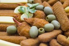 Piatti di pesce fritti decorati con le olive verdi Immagini Stock